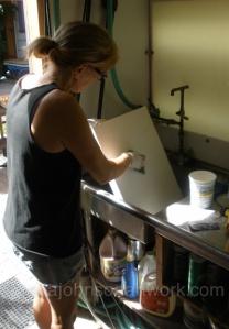 Jana sanding primed canvases